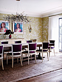 Long dining table with bordeaux-red upholstered chairs in the dining room with wallpaper