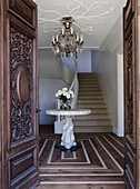 Elegante Eingangstür mit Holzschnitzerei aus dem 19. Jahrhundert, runder Marmortisch in der Eingangshalle