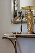 Elegant console with table lamp in front of wall mirror with silver frame