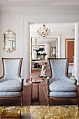 French armchairs with side table and coffee table in gold in elegant salon