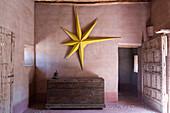 Gelber Stern an der Wand über einer alten Truhe im Lehmhaus
