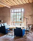Blaue Polstermöbel vor dem Fenster im marokkanischen Lehmhaus