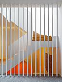 Weiß gestrichene Metallstangen als Raumteiler, Blick auf Treppenhaus