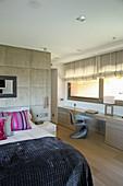 Modern bedroom in beige with long desk below windows