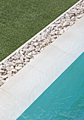 Straight lines formed by lawn, pebbles, pool surround and water