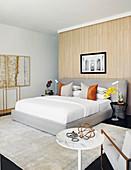 Doppelbett in hellem Schlafzimmer, im Vordergrund Beistelltisch und Sessel