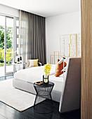 Beistelltisch neben Doppelbett in hellem Schlafzimmer mit Terrassenzugang
