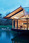 Woman sitting at table in illuminated architect-designed house on lake