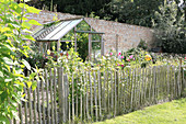 Paling fence surrounding cottage garden with greenhouse