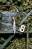 Anemones and heart-shaped wreath of ivy berries on old watering can