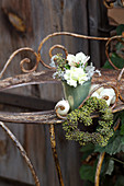 Posy and heart-shaped wreath of ivy berries on old metal table