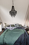 Bed with dark bed linen below chandelier in tent