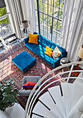 View down onto bright blue sofa and ottoman in double-height, open-plan interior