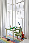Toys on child's table, chairs and guitar next to window in high-ceilinged room