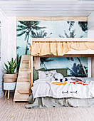 Wooden bunk bed in front of palm tree wallpaper in the children's room