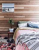 Double bed and bedside table with house plants in front of wall covering made from recycled cedar wood
