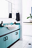 White bathroom with light blue vanity unit