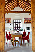 View through wooden columns into dining area and open-plan kitchen