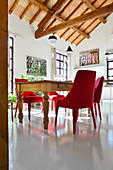 Modern red upholstered chairs around old wooden table below exposed roof structure