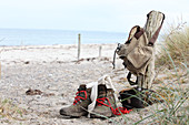 Walking boots, binoculars and rucksack on beach