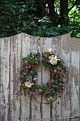 Wreath with flowers hung on rustic wooden fence in garden