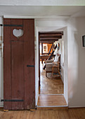 DIY sliding door made from old privy door with heart-shaped cutout