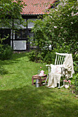 Blanket and cushions on old rocking chair and small table in garden