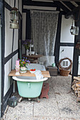 Candles and vase of flowers on bath caddy on bathtub on roofed veranda