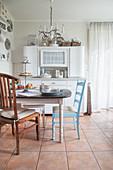 Küche in nordischer Stil: Essplatz vor altem, weißem Buffetschrank