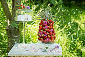Ananas mit Erdbeeren gespickt und Windlicht auf Gartentisch