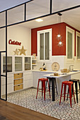 Open-plan kitchen in red, white and black with patterned floor