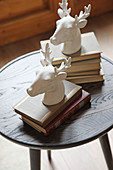 Stoneware stags heads on two stacks of books on small round table