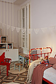 Fairy lights on red metal bed in child's bedroom with patterned floor