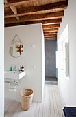 Simple white bathroom with wood-beamed ceiling