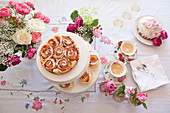 Apple rose tart, dome cake, coffee and arrangements of roses on table