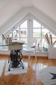 Desk made from old sewing machine base with glass top in front of triangular windows in gable