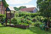 Wooden playhouse with slide, wicker raised beds and seating area below tree in garden