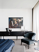 Designer armchairs and side table in front of sideboard in bedroom