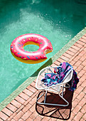Pool with swim hoops, chair with bath towel on the edge