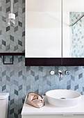 Wash basin with countertop basin, above it a wall tap and mirror cabinet, 3D tile pattern