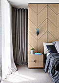 Wood veneer with an integrated bedside cabinet next to a double bed in the bedroom