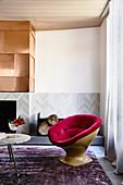 Designer-Sessel, Coffeetable und Kamin, darüber Kupferplatte im Wohnzimmer