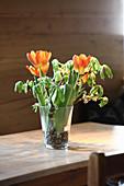 Tulpen und Äste in einer Glasvase mit Kieselsteinen
