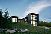 Cubist architect-designed house at twilight with illuminated glass walls