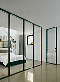 Glass and steel partition wall with door screening bedroom