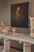 Painting on wall above angel figurines, urns and eggs on stone table