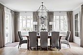 Grey upholstered chairs around wooden table in elegant dining room