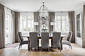 Graue Polsterstühle um einen Holztisch im eleganten Esszimmer