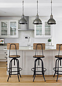 Industrial-style barstools at kitchen island with white base units
