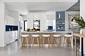 Barstools at island counter in modern kitchen with white cabinets
